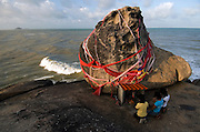 """Kao Seng fishing village (""""900,000 baht""""). Pilgrims wai the sacred stone which gives the fishing village of Kao Seng its name. Treasure said to be worth 900,000 baht is believed to lie beneath the boulder. It is supposed to have come from foreign merchants who kept it there for safe storage."""