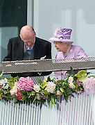 © Licensed to London News Pictures. 07/06/2014. Epsom, UK. HRH HRH Prince Philip The Duke of Edinburgh and Queen Elizabeth II watch the Derby from the balcony of the grandstand. Derby Day today 7th June 2014 at Epsom 2014 Investic Derby Festival in Surrey. Traditionally, elegant, fashionable racegoers gather for a classic day's racing at Epsom Racecourse, Surrey. Photo credit : Stephen Simpson/LNP