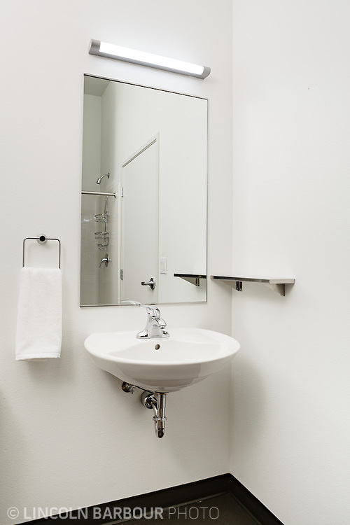University House student housing apartment in Eugene, OR. Designed by Mahlum Architects. A small sink installation in a bathroom showing the shower behind it in the mirror.