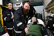 Hatzola are a voluntary medical emergency service that provides care to the Orthodox Jewish community of North London.  Here 3 of their volunteers provide care with oxygen to an Orthodox Jewish patient in the back of their ambulance.