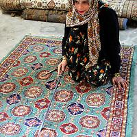 Asia, India, Jaipur. Woman displays an ethnic Indian carpet.