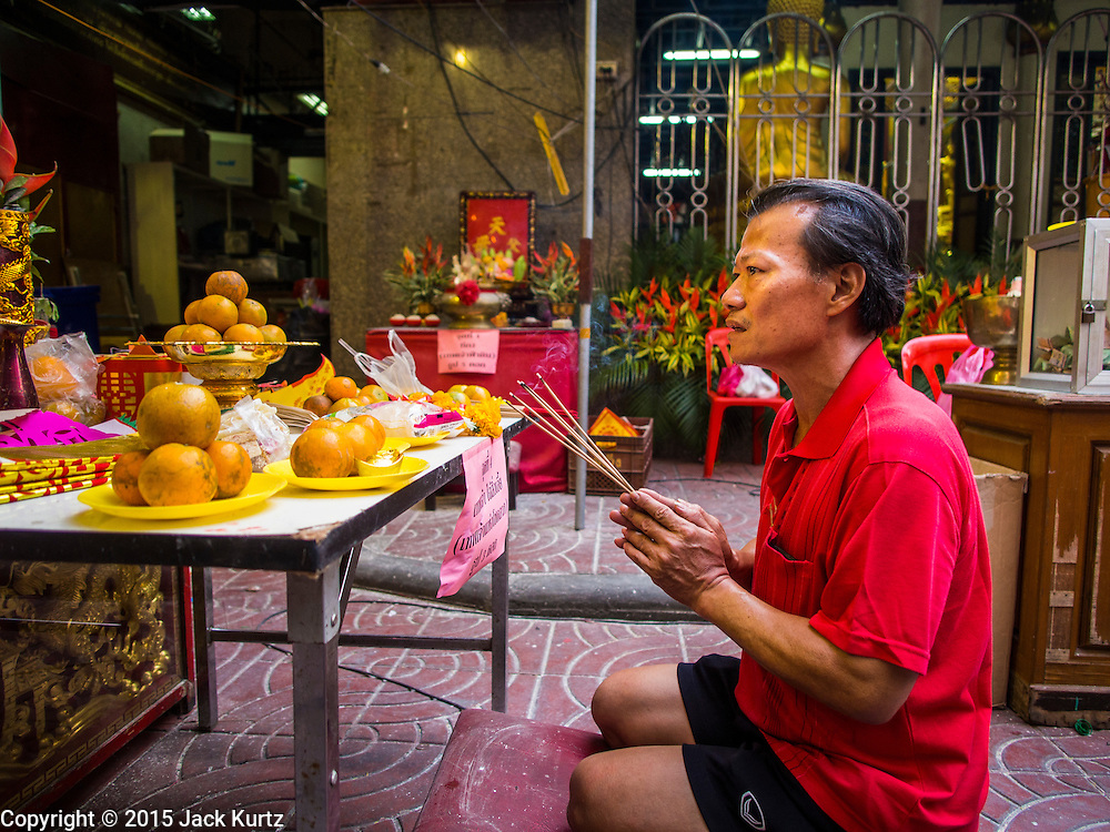 """19 FEBRUARY 2015 - BANGKOK, THAILAND:  A man prays at a Chinese shrine on Chinese New Year in Bangkok. 2015 is the Year of Goat in the Chinese zodiac. The Goat is the eighth sign in Chinese astrology and """"8"""" is considered to be a lucky number. It symbolizes wisdom, fortune and prosperity. Ethnic Chinese make up nearly 15% of the Thai population. Chinese New Year (also called Tet or Lunar New Year) is widely celebrated in Thailand, especially in urban areas that have large Chinese populations.    PHOTO BY JACK KURTZ"""