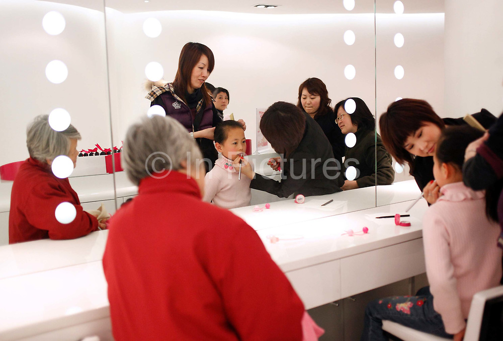 A young girl is the center of her relatives' attention as she gets makeup lessons at the new Barbie flagship store in Shanghai, China on 04 April, 2009. The six story store was opened in March this year to mark the 50th birthday of Barbie. The Barbie store has become a hit in Shanghai as a place where doting mothers take their daughters, often the only child in the family, for a girls' day out..