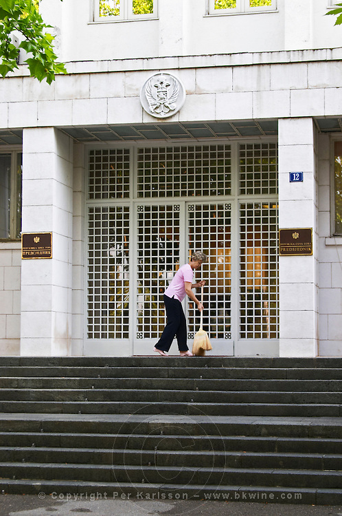 The presidential palace in Montenegro. The entrance. A woman sweeping cleaning with a broom in front of the door, on the Sveti Petra Saint Peter boulevard. Podgorica capital. Montenegro, Balkan, Europe.