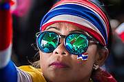 """08 APRIL 2014 - BANGKOK, THAILAND: The crowd is reflected in the sunglasses of an anti-government protestor in front of the Ministry of Justice in Bangkok. Several hundred anti-government protestors led by Suthep Thaugsuban went to the Ministry of Justice in Bangkok Tuesday. Suthep and the protestors met with representatives of the Ministry of Justice and expressed their belief that Thai politics need to be reformed and that corruption needed to be """"seriously tackled."""" The protestors returned to their main protest site in Lumpini Park in central Bangkok after the meeting.    PHOTO BY JACK KURTZ"""