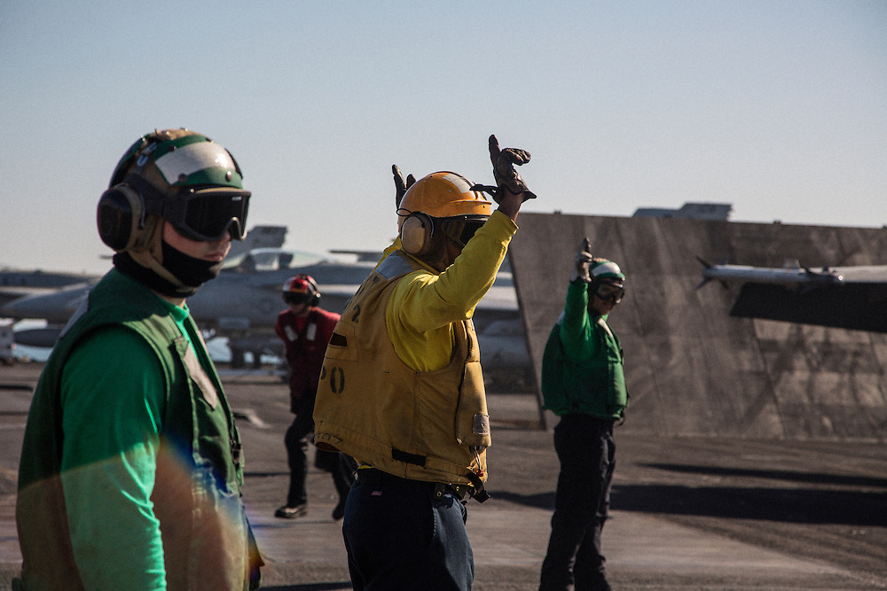 Flight deck crew use hand signals to ready an aircraft for launch<br /> <br /> Aboard the USS Harry S. Truman operating in the Persian Gulf. February 25, 2016.<br /> <br /> Matt Lutton / Boreal Collective for Mashable