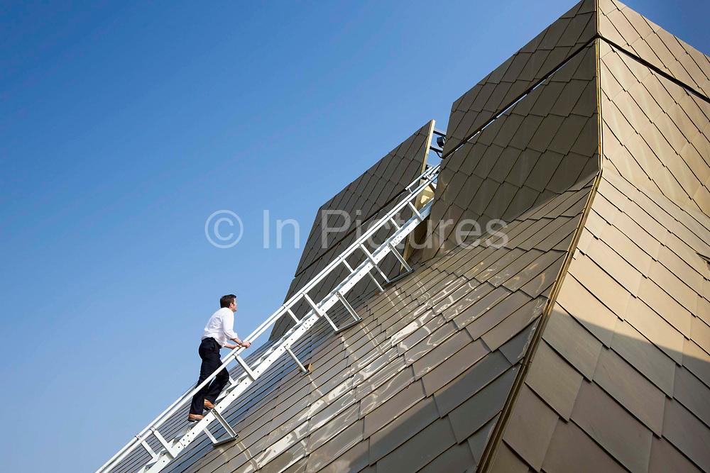 Guy Nevil, senior partner and engineer from Max Fordham climbing the distinctive gold coloured roof of  the Hive, Worcester is the first fully integrated university and public library in the UK. The distinctive roof cones serve to exhaust warm air and introduce daylight deep into the building.