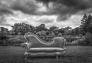 An ornate lounge sofa outdoors infront of a lake and house under dark clouds