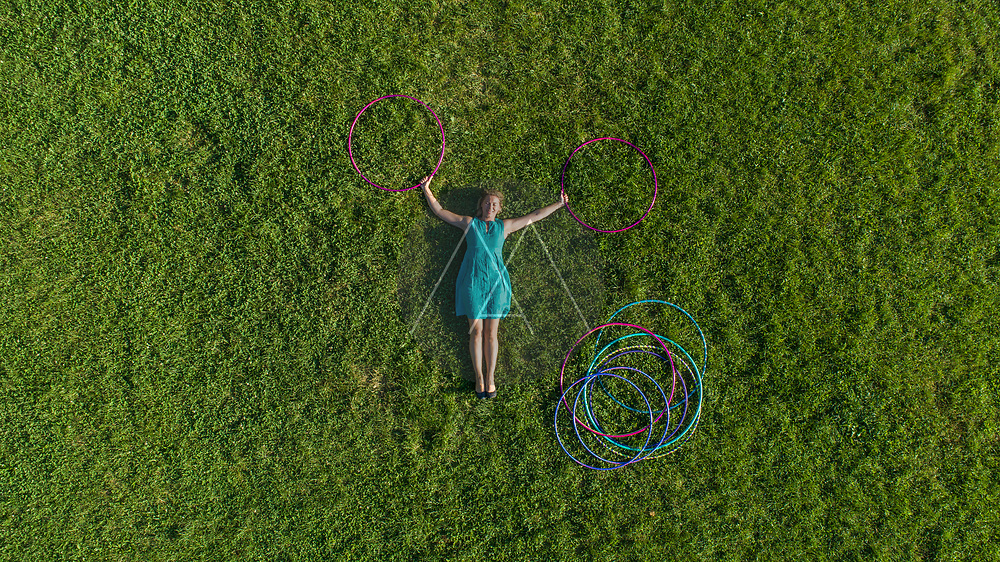 Aerial view of a woman laying on grass with Hola Hoop at public park in Zagreb downtown, Croatia.