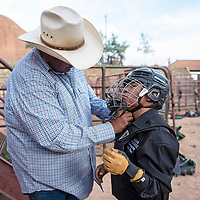 JR Etcitty helps his son Clint Etcitty, 10, fasten his helmet before he competes in steer riding, Wednesday, June 12 at Red Rock Park during the Gallup Lions Club youth rodeo.