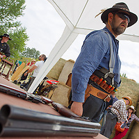 Participant watches the competition as his weapons lay on a table during the Cowboy Action Shooting European Championship in Dabas, Hungary on August 11, 2012. ATTILA VOLGYI