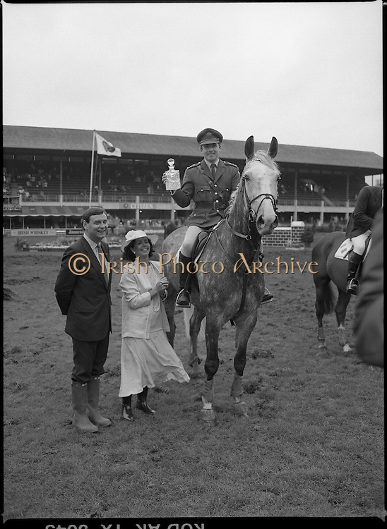 Jameson Whiskey International at the Dublin Horse Show.  (R39).1986..07.08.1986..08.07.1986..7th August 1986..The Jameson Whiskey International at the Dublin Horse Show in the RDS was won by Peter Charles of Great Britain. He rode 'Merrimandias' to victory in the event...Image shows Capt Gerry Mullins with the trophy presented to him by Mrs Marie Cummins, wife of the Managing Director, Irish Distillers. Capt Mullins the Irish Whiskey Classic aboard 'Glendalough'. Mr Michael Cummins also features in the picture. Jameson's, Irish, Whiskey, jameson,
