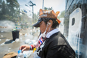 02 DECEMBER 2013 - BANGKOK, THAILAND:  An anti-government protestor takes shelter behind an abandoned police truck while police use water cannons against them in Bangkok. Anti-government protestors and Thai police continued to face off Monday for a second day. Police used tear gas, water cannons and rubber bullets against protestors who charged their positions near the barriers on Chamai Maruchet bridge on Phitsanulok Road, which leads to the Government House.    PHOTO BY JACK KURTZ