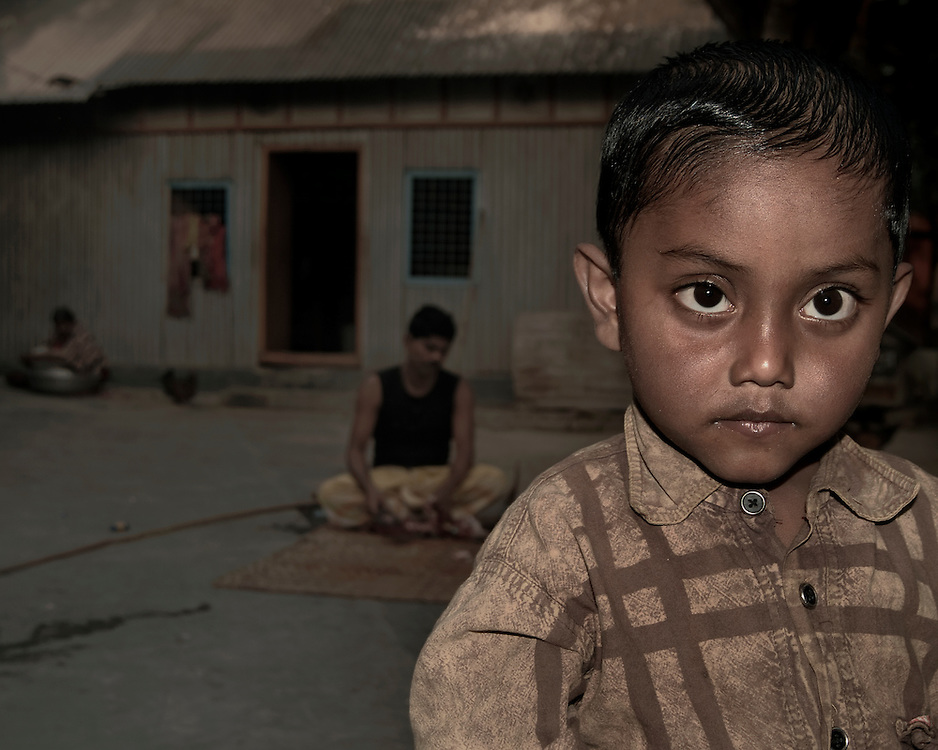 A boy with his family in the background in Asia