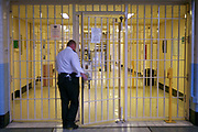 A prison officer going into C wing through a security gate inside HM Prison Wandsworth is a Category B men's prison at Wandsworth in the London Borough of Wandsworth, South West London, United Kingdom. It is operated by Her Majesty's Prison Service and is one of the largest prisons in the UK with a population over 1500 people. (photo by Andy Aitchison)