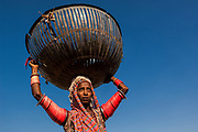 Gypsy woman carrying metal basket. These baskets are used for various things. Apart from carrying things they are used for protecting things from animals and children as well as to restrain young animals<br /> Rajasthan, INDIA