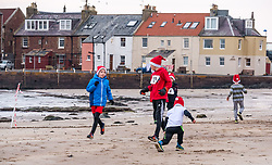 Pictured: Santa Beach Run on the scenic East Lothian coast. This new event is aimed at athletes, casual runners and families. It is hosted by Project Trust with proceeds enabling local school leavers to spend a year volunteering in India/Honduras to teach at a school with few teaching materials. Children limber up before their 2km race. A liitle boy does some stretches. 15 December 2018  <br /> <br /> Sally Anderson | EdinburghElitemedia.co.uk
