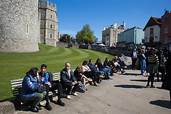 Windsor, UK. 17th April, 2021. Members of the public sit outside Windsor Castle on the day of the funeral of the Duke of Edinburgh. The funeral of Prince Philip, Queen Elizabeth II's husband, is taking place at St George's Chapel in Windsor Castle, with the ceremony restricted to 30 mourners in accordance with current coronavirus restrictions.
