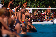 A multi-ethnic crowd enjoys a heatwave in the Herne Hill lido, south London, England. A mixture of cultural backgrounds and ethnicities celebrate the warm weather together either in the waters or on the poolside concrete. The water is blue and the skin is either white, sunburned pink or black afro-Carribean. The laughter is genuine with these Londoners relishing this local open-air mecca for healthy sun worship. This lido was opened in July 1937, closed in 1990 and after a local campaign was re-opened in 1994. Brockwell Lido was designed by HA Rowbotham and TL Smithson of the London County Council's Parks Department to replace Brockwell Park bathing pond.