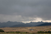 Rain falls on the Montana landscape, just ouostide Bozeman. The Gallatin Mountain range behind sits beneath Montanas famous grey cloud filled big sky, which coins the name of Big Sky Country, whatever the weather.