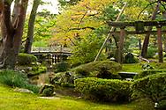 Hanambashi Bridge and a stone gate surrounded by autumn foliage in the Kenrokuen Garden, Kanazawa, Ishigawa, Japan