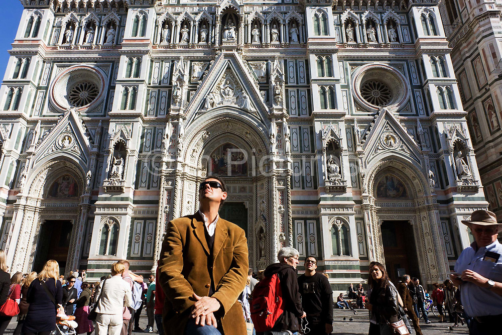 Behind the viewer, tourists gaze upwards to the Baptistry of San Giovanni beneath Florence's Santa Maria del Fiore (Duomo) Cathedral. Hundreds of worldwide visitors tour the Piazza San Giovanni to see the Duomo and Giotto's Belltower. The dramatic Basilica di Santa Maria del Fiore is the cathedral church (Duomo) of Florence, Italy, begun in 1296 in the Gothic style to the design of Arnolfo di Cambio and completed structurally in 1436 with the dome engineered by Filippo Brunelleschi.