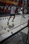 A jogger runs past an office foyer entrance featuring dots and circles (and shadows) on exterior windows in the City of London.