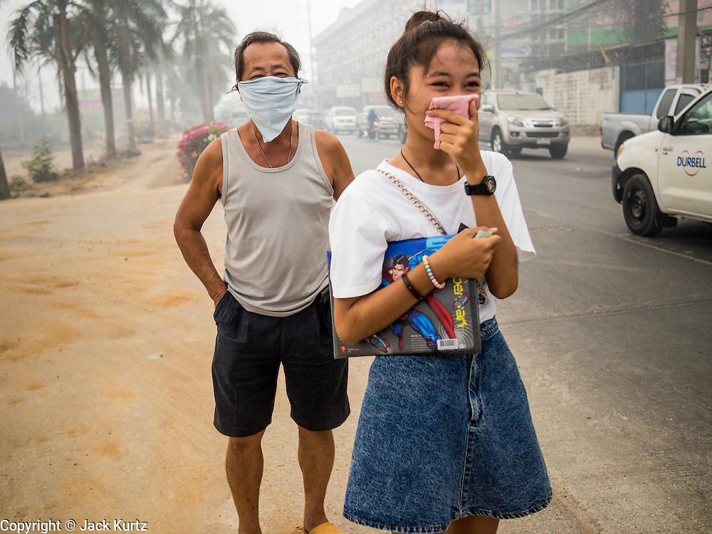 17 MARCH 2014 - PHRAEKSA, SAMUT PRAKAN, THAILAND: People in Phraeksa, Samut Prakan province, wearing breathing filters because of the heavy smoke over the city from a fire in a nearby landfill. A fire apparently spontaneously started in the landfill in Samut Prakan over the weekend and threatens the homes of workers who live near the landfill. The fire Officials said the fire started when garbage in the landfill burst into flames and the flames were spread by hot, dry winds. Hundreds of people have been evacuated because of the fire and acrid smoke from the fire has spread as far as Bangkok. It hasn't rained in central Thailand in more than three months, impacting agriculture and domestic water use. Many farms are running short of irrigration water and salt water from the Gulf of Siam has come up the Chao Phraya River and infiltrated the water plants in Pathum Thani province that serve Bangkok.   PHOTO BY JACK KURTZ