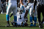 Teammates help pick Carolina Panthers quarterback Cam Newton (1) off the ground after being knocked down by the Oakland Raiders defense at Oakland Coliseum in Oakland, Calif., on November 27, 2016. (Stan Olszewski/Special to S.F. Examiner)