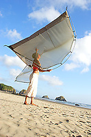 Young woman shaking out tent while camping on a secluded beach along the Oregon Coast. Cannon Beach, OR
