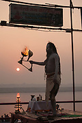 A Saddhu worships on the banks of the Ganges at dawn on 21st December 2009, Varanasi / Benares, Uttar Pradesh, India. According to Hindu mythology, Varanasi was founded by Shiva, one of three principal deities along with Brahma and Vishnu, and is seen as a significant and holy place to followers of the Hundu faith. .