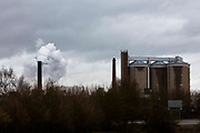 Steam bellows from the chimney of the British sugar beet processing plant in Newark on Trent, Nottinghamshire, United Kingdom.