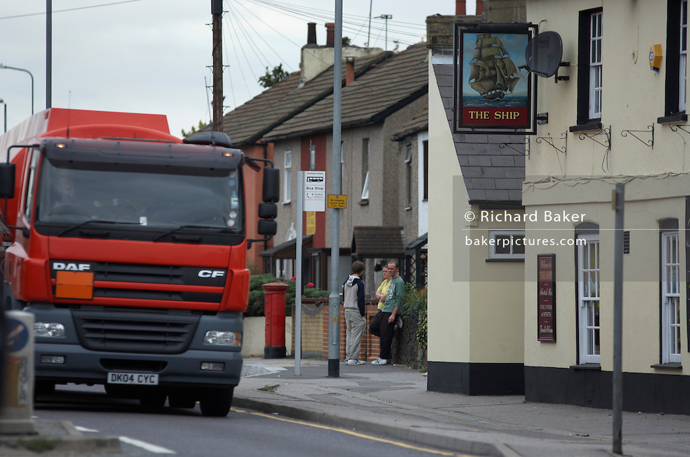 A Heavy Goods Vehicle (HGVs) thunders past houses and The Ship pub on the A126 in industrial Grays, Thames Gateway