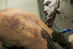 October 5, 2018 - Barcelona, Catalonia, Spain - Tattoo artist makes a tattoo in the back during the 21st tattoo and urban culture Expo in Barcelona. (Credit Image: © Celestino Arce Lavin/ZUMA Wire)