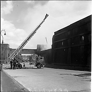 05/07/1961<br /> 07/05/1961<br /> 05 July 1961<br /> A fire at Powers Distillery, John's Lane, Dublin. The fire fortunately occurred during a period when the distillery was not in use, but a warehouse containing 4000 hogsheads of maturing whiskey was destroyed. Picture shows Firemen and fire engine using the trucks ladder and hose to combat the fire.