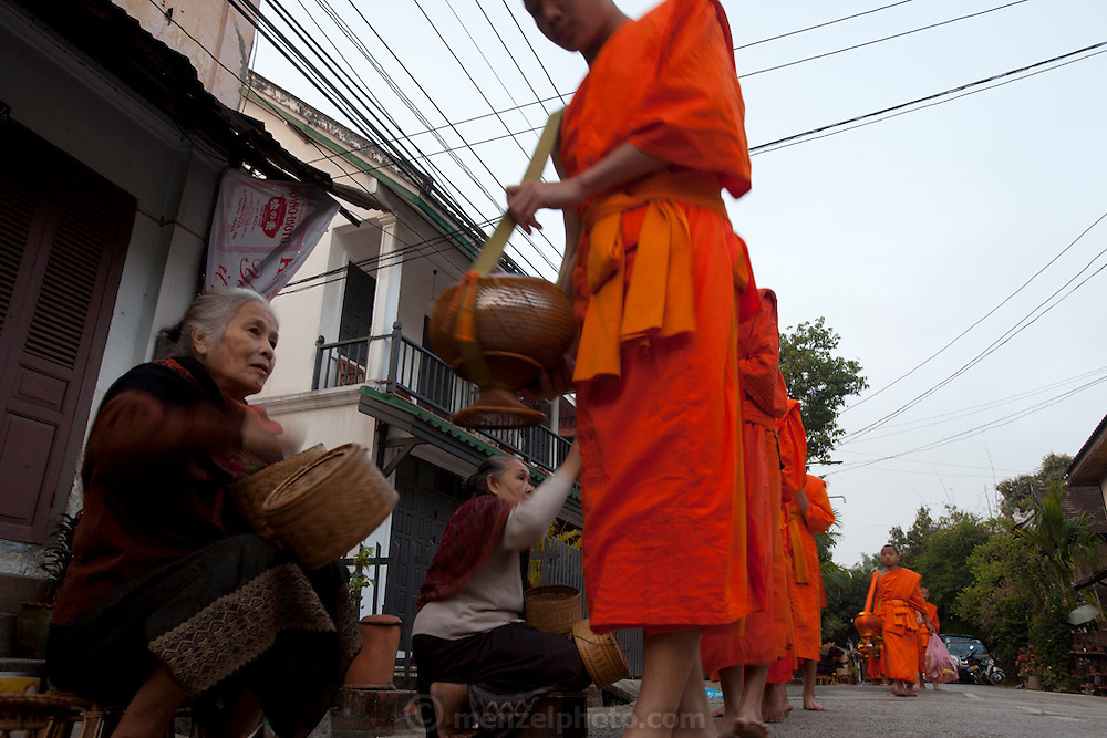 """Luang Prabang, Laos. Every morning at dawn, barefoot Buddhist monks and novices in orange robes walk down the streets collecting food alms from devout, kneeling Buddhists. They then return to their temples (also known as """"wats"""") and eat together. This procession is called Tak Bat, or Making Merit."""