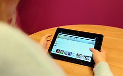PICTURE POSED BY MODEL A generic stock photo of a woman using a Kindle Fire HDX 8.9 tablet.