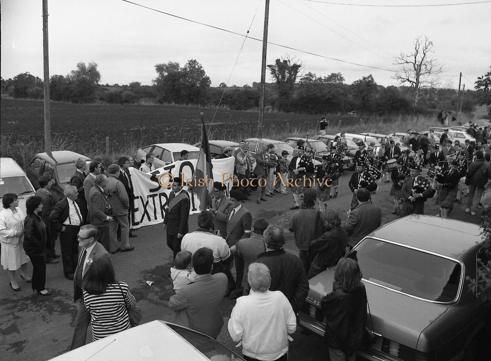 Annual Wolfe Tone Commemoration.  (R65)..1987..11.10.1987..10.11.1987..11th October 1987..The annual Fianna Fáil Wolfe Tone commemoration was held at Bodenstown today, the keynote oration was given by An Taoiseach, Charles Haughey TD...Picture shows the Narraghmore,Co Kildare pipe band leading the procession into Bodenstown for the Wolfe Tone commemoration, past the Stop Extradition protest.