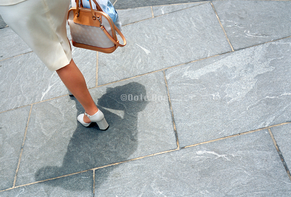 Stylish woman in white heels walking on the pavement