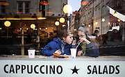 A brother and sister share a hot chocolate drink in a London branch of the sandwich lunch chain Pret a Manger.