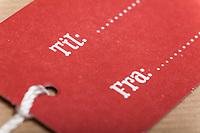 Gavelapp med tekst «til…» og «fra…». Rødfarge hinter om jul. Rustikk stil.