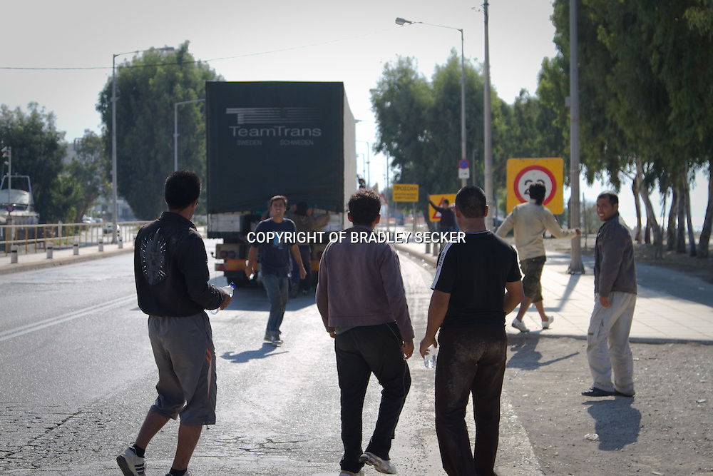A group of migrants from Afghanistan and Pakistan watch as their friends successfully smuggle themselves inside a lorry headed for Italy. The 'runway' Patras, Greece. October 2010