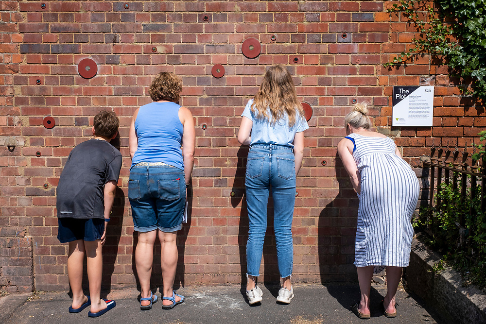People enjoying Looking Ahead by artist Jacqueline Poncelet for the Creative Folkestone Triennial 2020, The Plot on 21st of July 2021, in Folkestone, United Kingdom. Looking Ahead pierces holes through the brick of the retaining wall of the old Ship Street gasworks. A variety of lenses have been fitted into the holes, including some that mimic bee-eyes, as well as mechanically operated kaleidoscopes. Viewers will be afforded an extraordinary and ever-changing view over the gasworks site, the railway viaduct and the hills, as well as the future. Folkestone's 5th open air art exhibition The Plot sees 27 newly commissioned artworks appearing around the south coast seaside town. The new work builds on the work from previous triennials making Folkestone the biggest urban outdoor contemporary art exhibition in the UK.  (photo by Andrew Aitchison / In pictures via Getty Images)