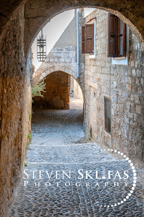 Rhodes. Greece. Narrow quiet arched pebble stone laneway inside the old walled medieval town of Rhodes.