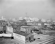 """Simon 114.  view of downtown Portland from the Hawthorne Bridge, after the construction of the Seawall in 1927. The buildings in the foreground were demolished to make way for the Portland Public Market Building in 1933. (note billboard advertising """"7th Western Divisional meeting of the Chamber of Commerce of the USA"""" which was held at Ogden, Utah, on October 1, 1929. billboard advertising """"Powers for more than 60 years. Their 60th anniversary was 1926. In all likelihood, this dates from the summer of 1929.)"""