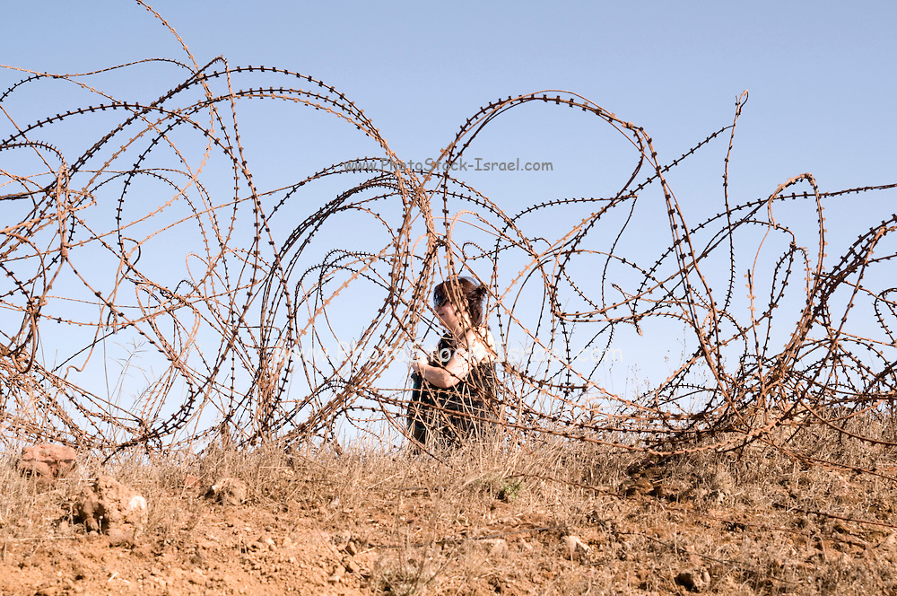 Woman, in her forties, confined by a Barbed wire fence