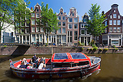 Canal tour cruise barge boat  takes tourists group by canalside gabled houses - Dutch gables - Brouwersgracht, Amsterdam, Holland