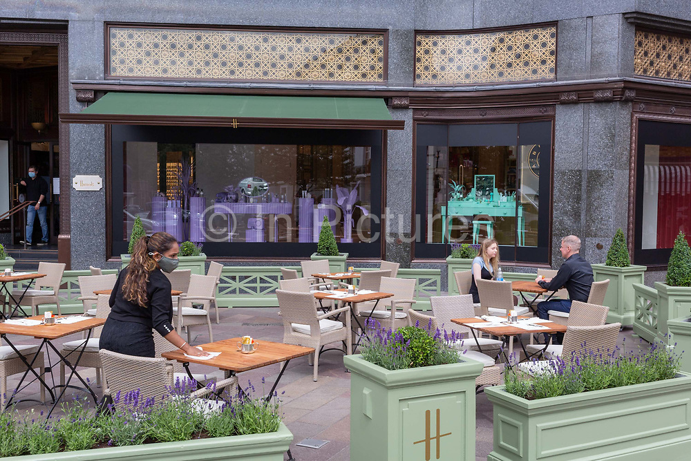 On the day that covid pandemic guidelines for shoppers in England mean that the wearing of face coverings in shops becomes mandatory, a waitress wearing a face covering wipes down table surfaces near customers outside Harrodss in Knightsbridge, on 24th July 2020, in London, England.