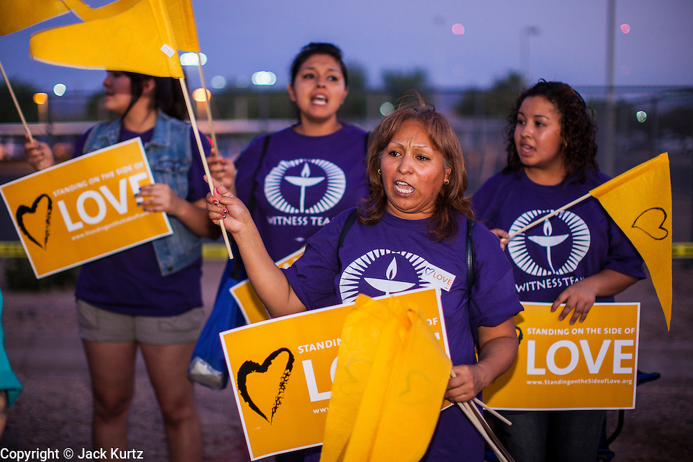 """23 JUNE 2012 - PHOENIX, AZ:  Members of the Unitarian Church picket the Maricopa County Jail in Phoenix. About 2,000 members of the Unitarian Universalist Church, in Phoenix for their national convention, picketed the entrances to the Maricopa County Jail and """"Tent City"""" Saturday night. They were opposed to the treatment of prisoners in the jail, many of whom are not convicted and are awaiting trial, and Maricopa County Sheriff Joe Arpaio's stand on illegal immigration. The protesters carried candles and sang hymns.      PHOTO BY JACK KURTZ"""