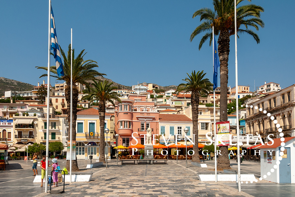 Samos. Greece. Main Square known as Plateia of Pythagorou of Vathy or Samos town. Vathy is situated on a horseshoe shaped bay and is the capital and largest town of Samos. Its bustling palm tree lined waterfront has certain faded elegance and is adorned with neo-classical buildings many topped with red tiled roofs and the town rises steeply into wooded hills above.
